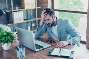 Homme devant son ordinateur se tenant la tête avec la main